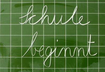 Symbolbild Schulanfang -  Mit Kreide auf eine Tafel geschriebener Text 'Schule beginnt'.
